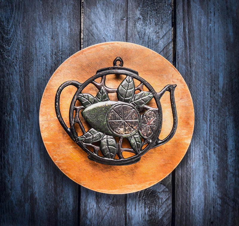 Vintage iron stand in form of a tea pot on circle board and blue wooden background, tea concept royalty free stock images