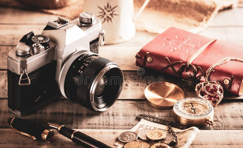 Vintage items, pen red book, coins money, compass and retro photo film camera on wood background.  stock photo