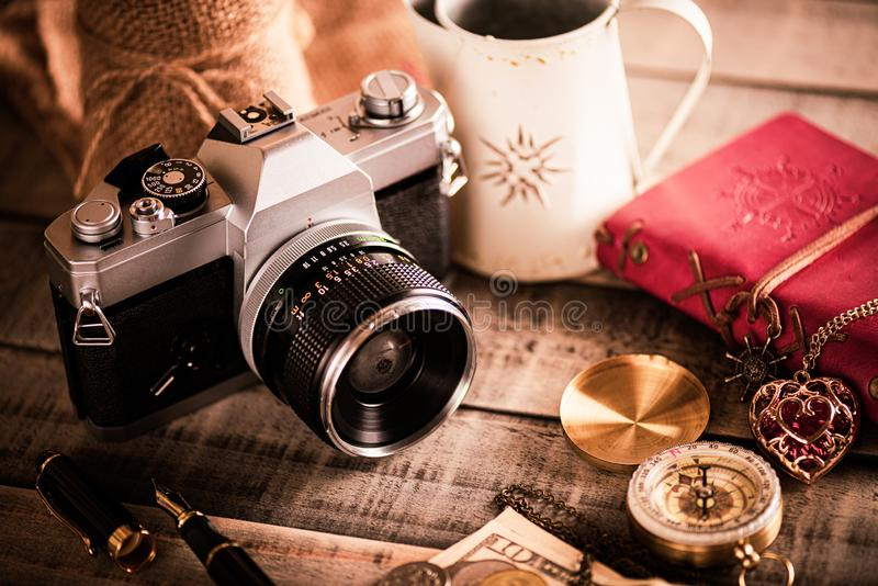 Vintage items, pen red book, coins money, compass and retro photo film camera on wood background.  stock photos