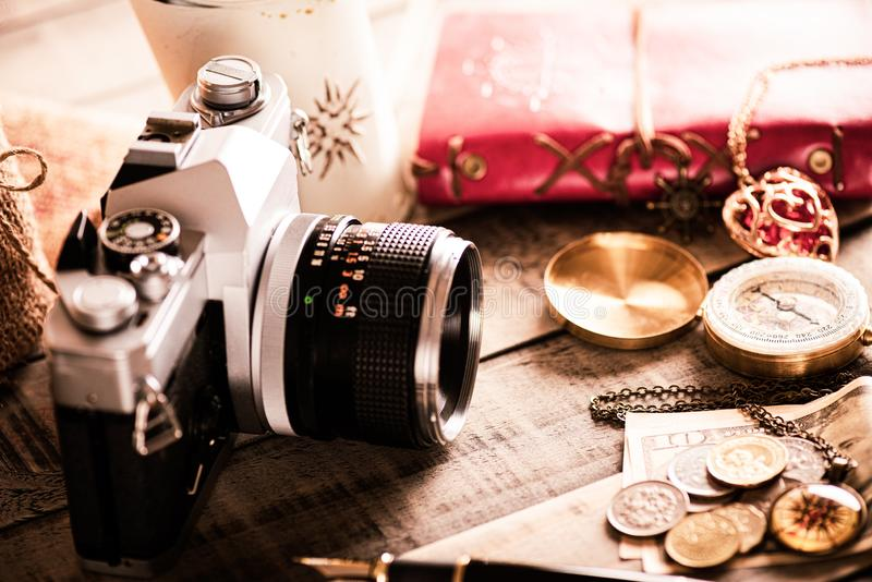 Vintage items, pen red book, coins money, compass and retro photo film camera on wood background.  royalty free stock images