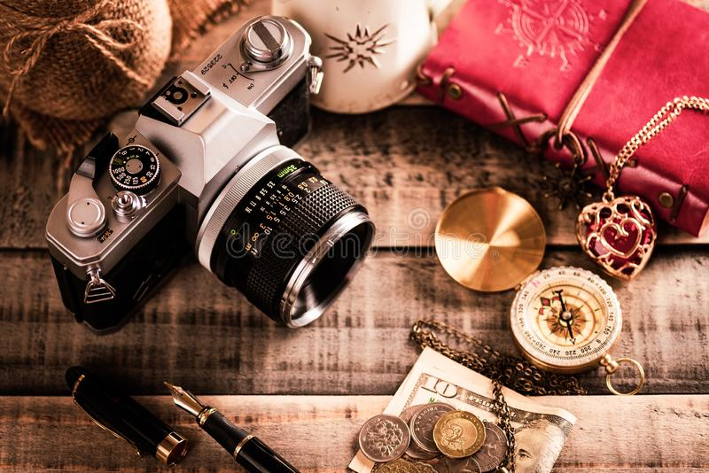 Vintage items, pen red book, coins money, compass and retro photo film camera on wood background.  stock image