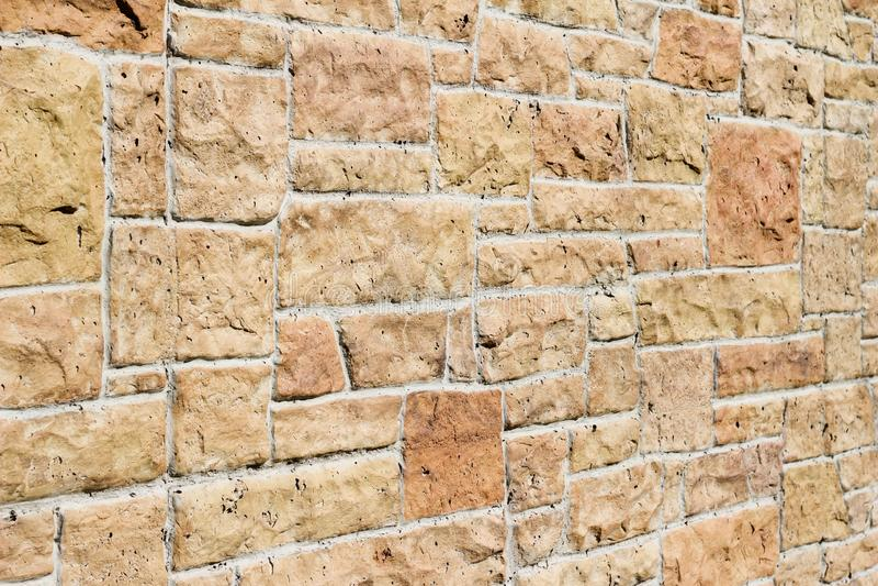 Vintage kasota limestone brick wall texture in colors of orange and pink beige stock photo
