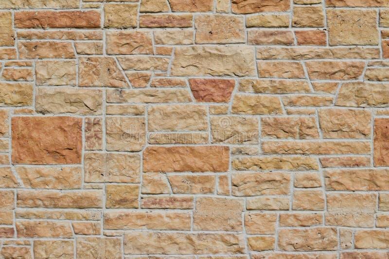 Vintage kasota limestone brick wall texture in colors of orange and pink beige royalty free stock image