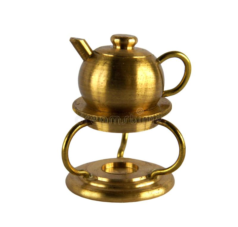 Vintage kettle on the stand. Brass figurine or miniature of vintage kettle on the stand isolated on white background stock photo