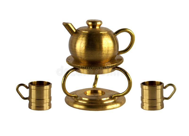 Vintage kettle on the stand and two cups. Brass figurine or miniature of vintage kettle on the stand and two cups isolated on white background royalty free stock image