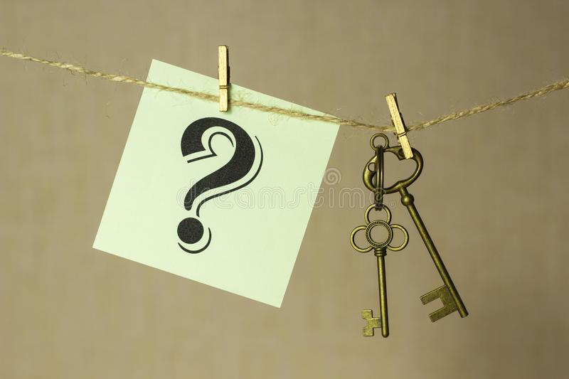Vintage key hanging on a rope on a gold background, next sticker with question mark royalty free stock photography