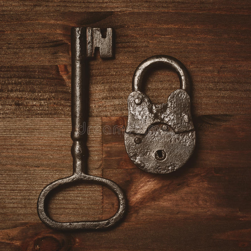 Vintage key and lock on a wooden background. Rare objects. Retro items of the late 19th - early 20th century royalty free stock photography