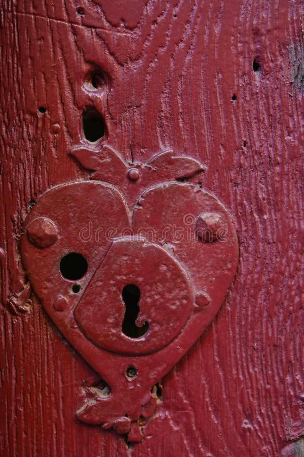 Vintage keyhole in an old red door stock image