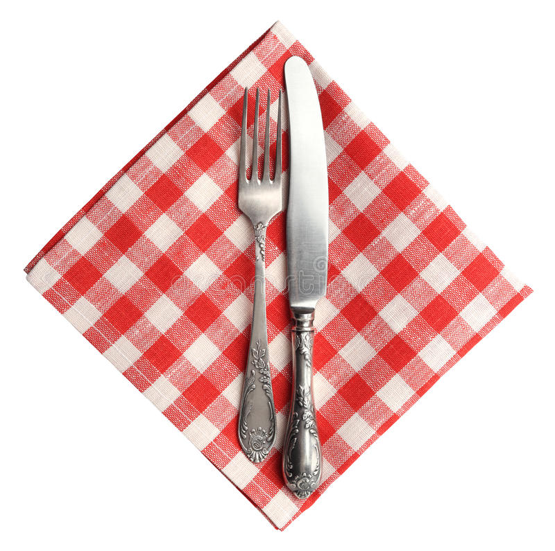Vintage knife and fork on red plaid linen napkin isolated. Vintage knife and fork on red plaid linen napkin isolated on white background royalty free stock images