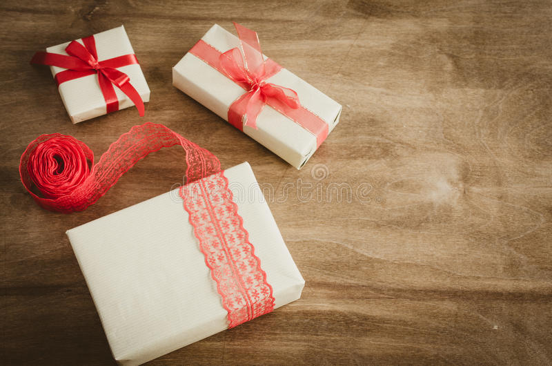 Vintage kraft boxes with gifts, tied with red ribbons on rustic wooden background. royalty free stock images