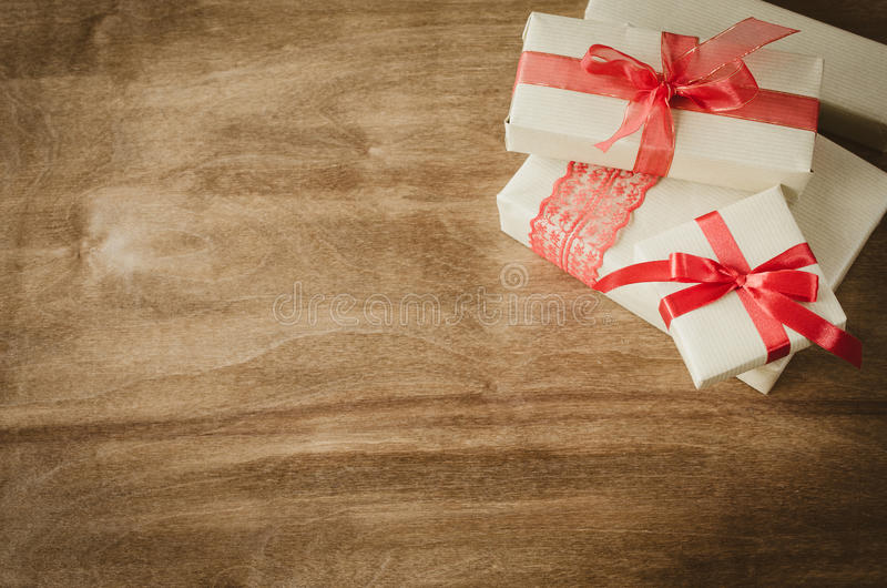 Vintage kraft boxes with gifts, tied with red ribbons on rustic wooden background. stock image