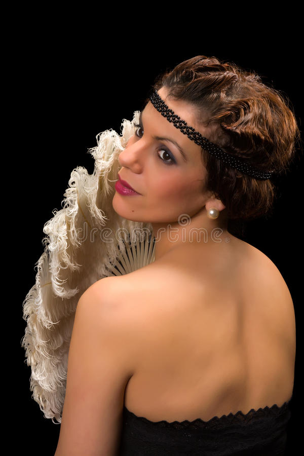 Vintage lady with antique feather fan. Glamour style vintage 1920 actress posing like a diva royalty free stock photography