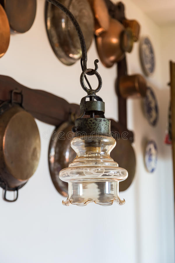 Vintage lamp on the background wall with antique copper utensils stock photo