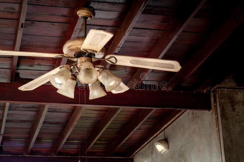 Vintage lamp with ceiling fan. Vintage lamp with rotating ceiling Fan in wooden house royalty free stock photography