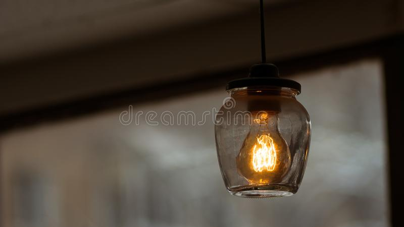 Vintage lamp in the glass jar. A vintage lamp in glass jar indoors. Lamp is just warm and beauiful royalty free stock images