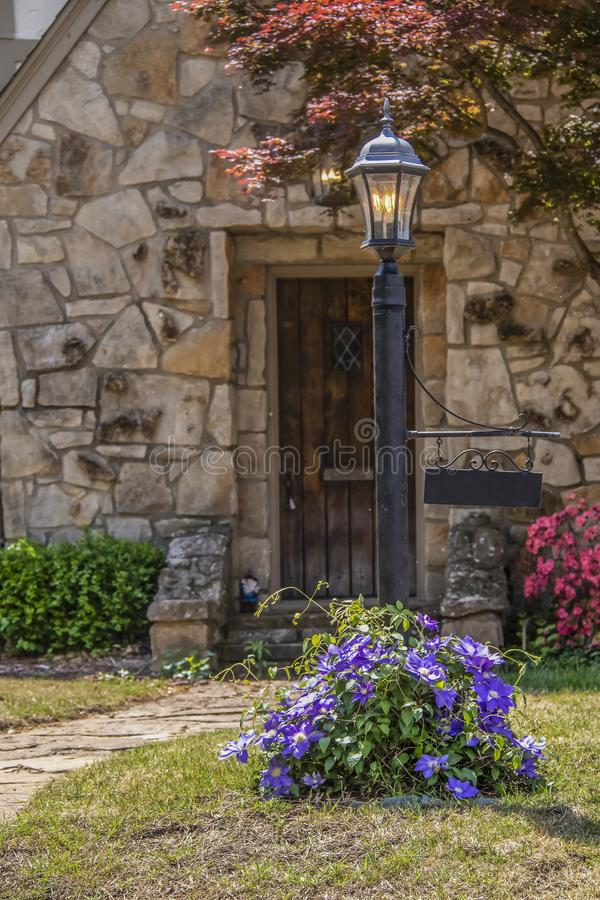 Vintage lamp post with purple clematis full of blooms vining around the bottom of it and rustic rock cottage door blurred behind stock image