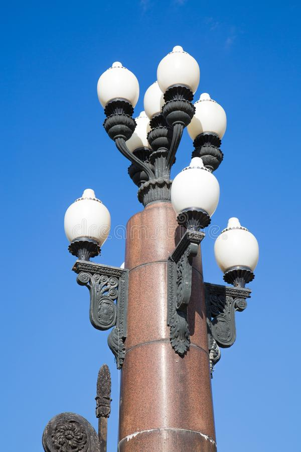 Vintage lamps in the form of a vase located on a column of brown granite against the blue sky. Architecture details the elements of the design stock photo