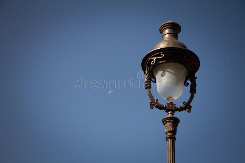Vintage lantern on the background of a clear blue sky and a translucent rising moon, Paris, Montmartre. Light vignette, free space for text stock photos