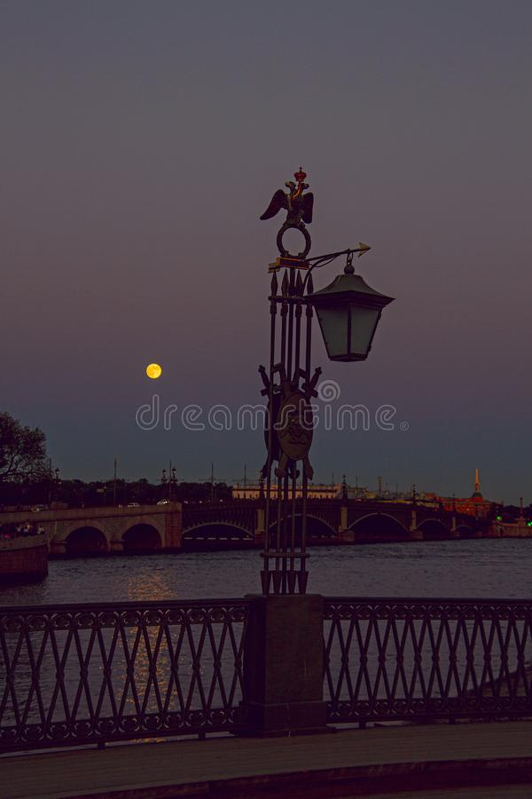 Vintage lantern by the river at dusk. Vintage lantern on the riverbank at dusk in the light of the full moon royalty free stock photos