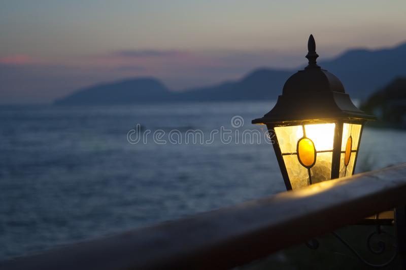 Vintage lantern shines at sunset in the background of the sea stock photo