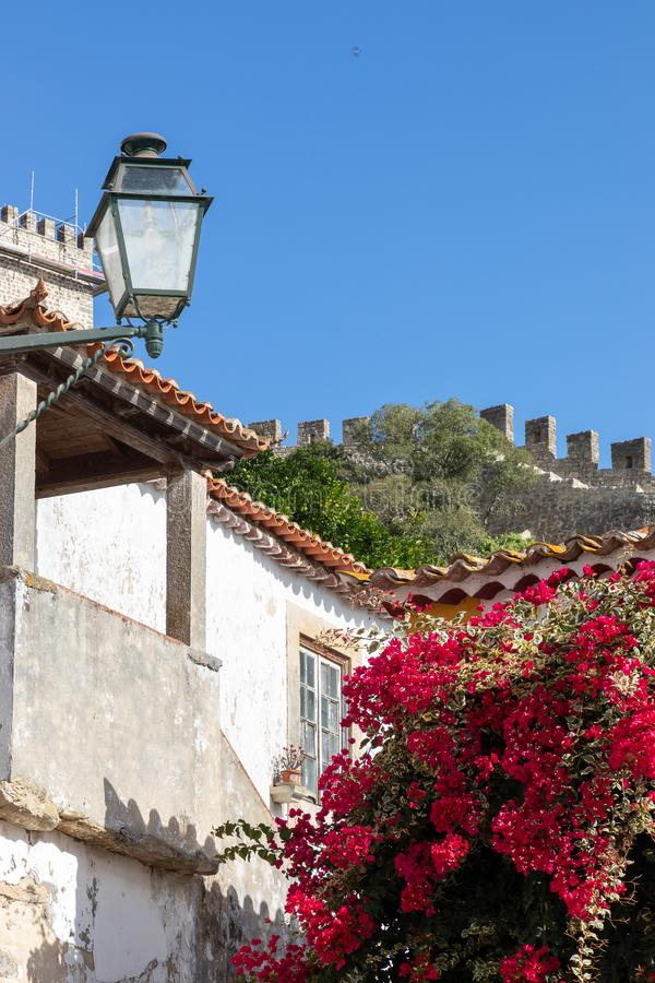 Vintage lantern on white stucco house with red bougainvillea flowers in bloom and ancient town wall of Obidos, Portuga royalty free stock photos