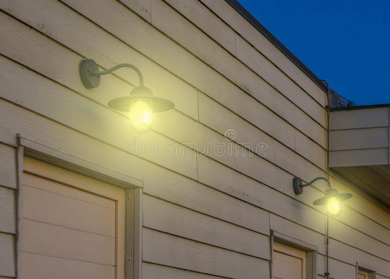 Vintage lanterns hanging on a wooden wall of a vintage home, outdoor lighting in retro style, lamps shining light in the dark,. Some Vintage lanterns hanging on stock photography