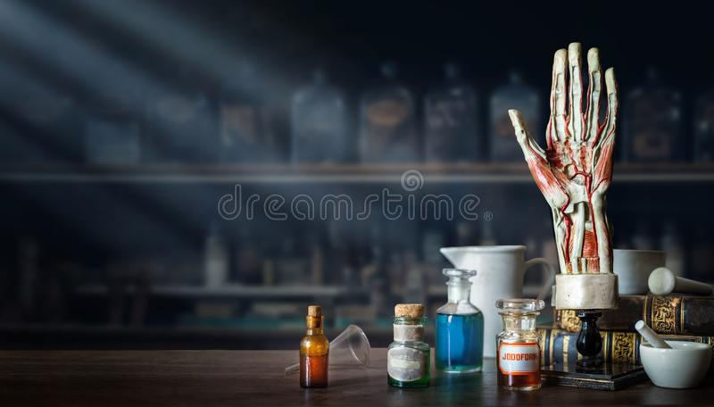 Vintage layout of a man`s hand, old medical glass bottles, antique medical tools on the background of a medical office. Old royalty free stock images