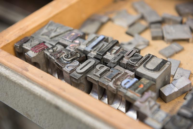 Vintage lead letterpress printing blocks against a weathered wooden drawer background with bokeh stock photography