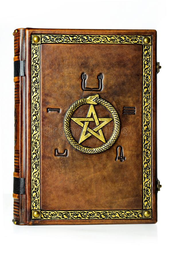 Vintage leather book with gilded ouroboros, pentagram and embossed five elements symbols on the ancient Egyptian. stock images