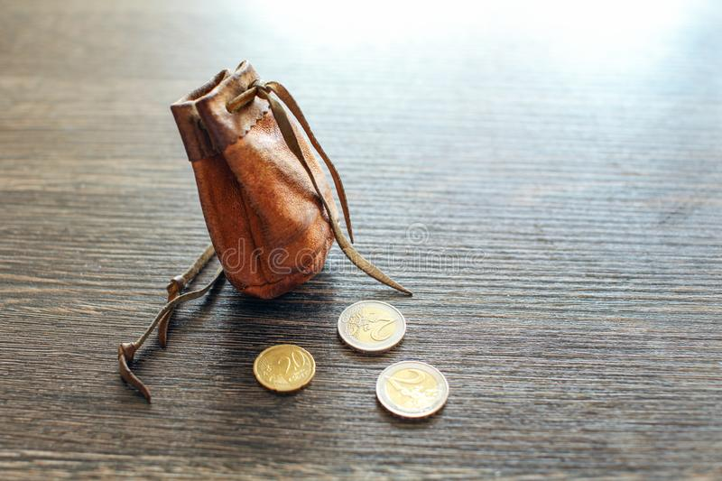 Vintage leather pouch on wooden desk, with euro coins next to it.  stock image