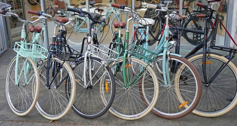 Vintage Lekker bicycles parked nicely in a row outside bike shop. stock image