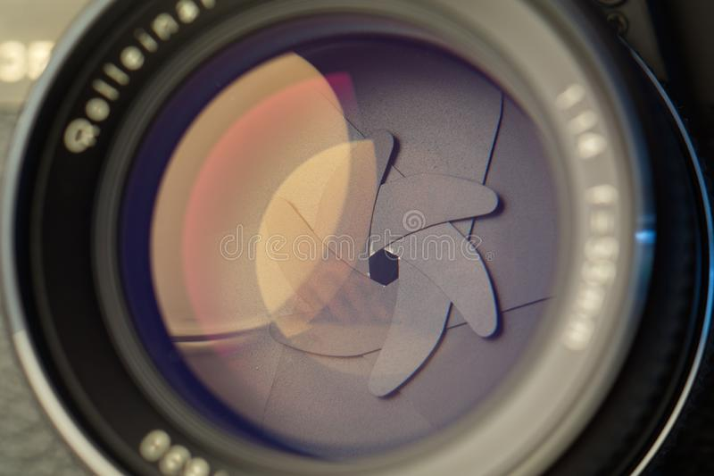 Vintage lens front element close up macro shot with light reflections and visible closed  aperture blades royalty free stock photo