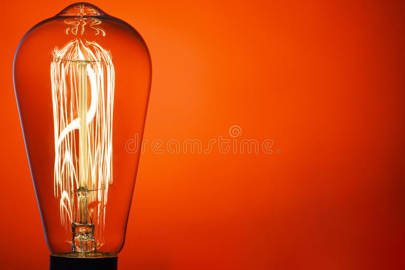 Vintage light bulb, on bright red background. Abstract composition. Old style. IDEA!!! Place for Your text royalty free stock photography