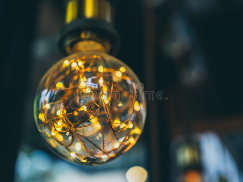 Vintage light bulb in cafe. Decorative antique edison vintage style light bulbs on cafe background with copy space royalty free stock image