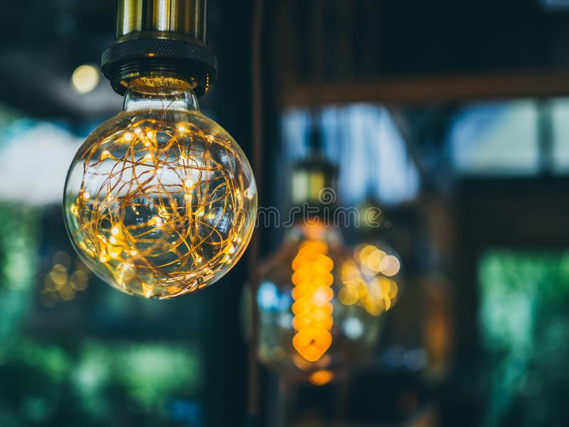 Vintage light bulbs in cafe. Decorative antique edison vintage style light bulbs on green garden in cafe background royalty free stock photos