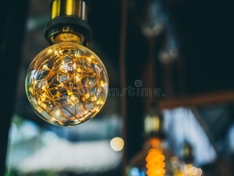 Vintage light bulbs in cafe. Decorative antique edison vintage style light bulbs on green garden in cafe background royalty free stock photography