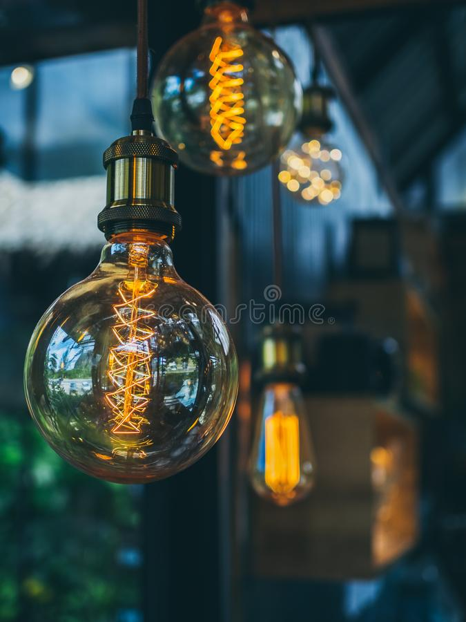 Vintage light bulbs in cafe. Decorative antique edison vintage style light bulbs on cafe background with copy space vertical style stock image
