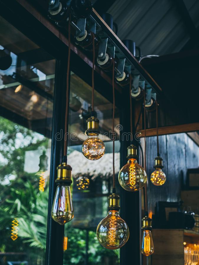 Vintage light bulbs in cafe. Decorative antique edison vintage style light bulbs on green garden in cafe background stock images