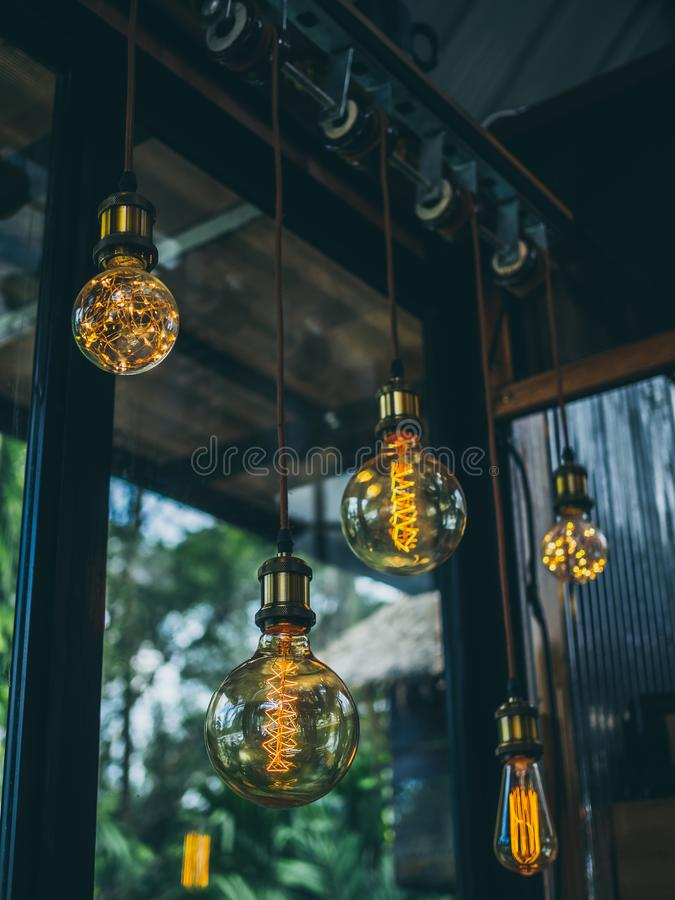 Vintage light bulbs in cafe. Decorative antique edison vintage style light bulbs on green garden in cafe background stock image