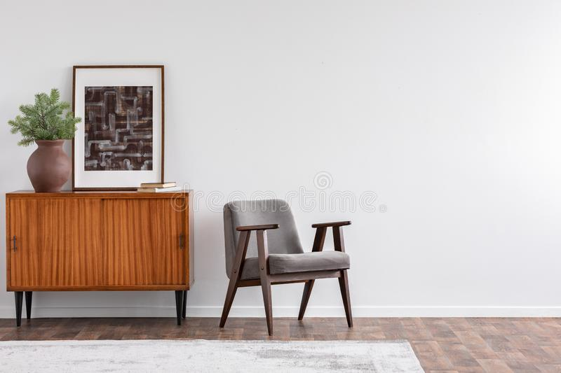 Vintage living room interior with retro furniture and poster, real photo with copy space on the white wall royalty free stock images