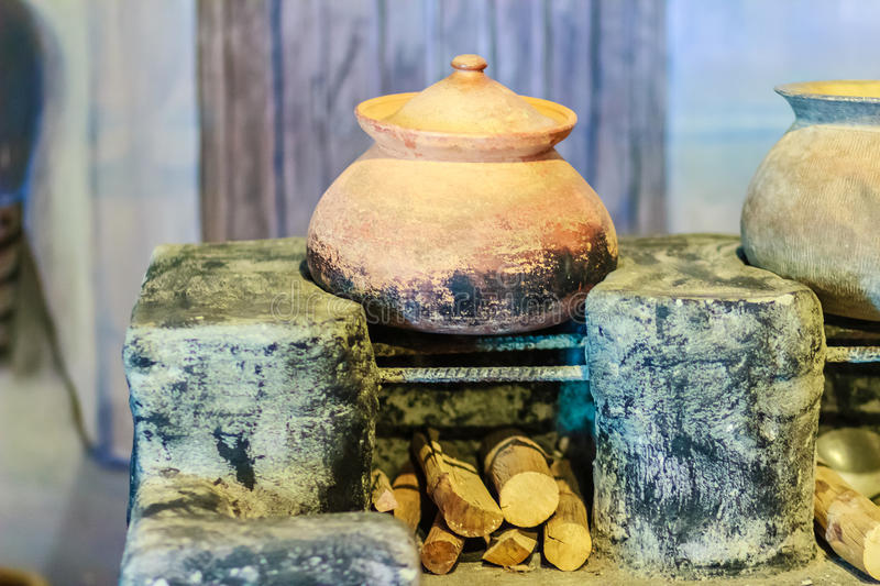 Vintage local kitchen area with old porcelain pot on the antique. Stove and firewood stock photography