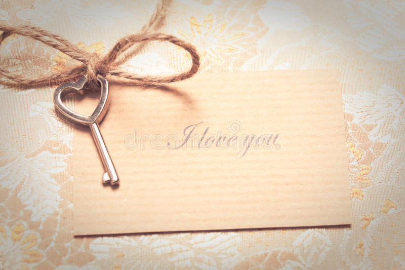 Vintage love card. Heart shaped key tied with a rope to a love card in a vintage style. Valentines card stock image