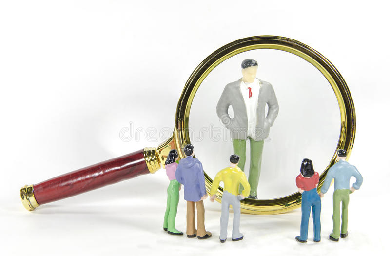Vintage magnify glass with Big Business man and small people model toy. A vintage magnify glass with Big Business man and small people model toy stock photos