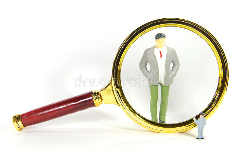 Vintage magnify glass with big and small business man. A vintage magnify glass with big and small business man stock photos