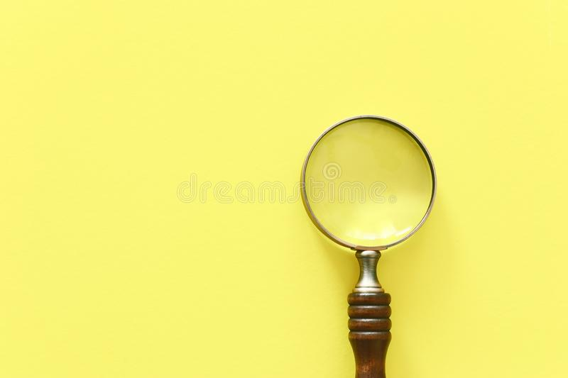 Vintage magnifying glass with wooden handle over yellow background. top view, flat lay.  royalty free stock images