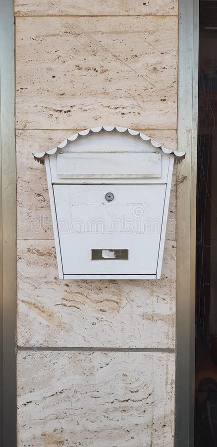 Vintage mail box closed with a key hang on stone building wall stock photography