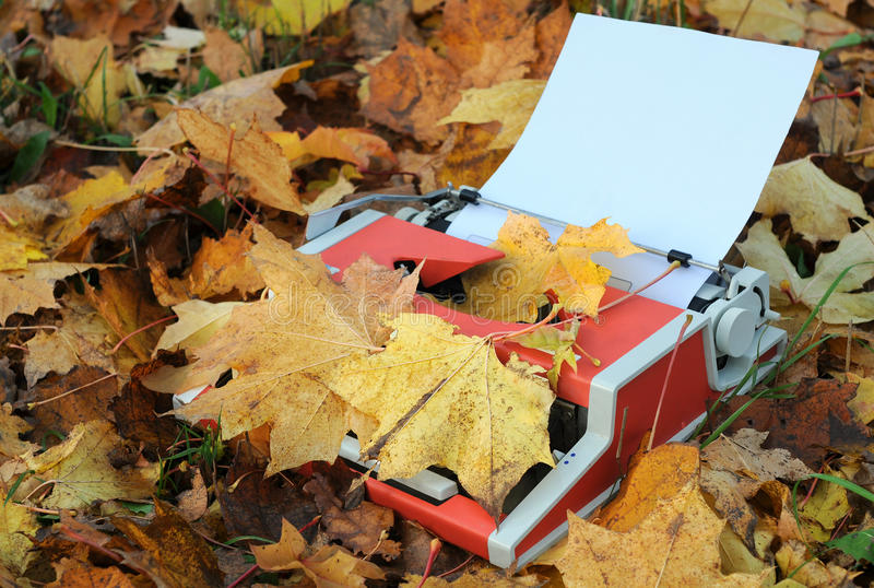 Vintage Manual Typewriter. Vintage shabby manual typewriter, blank sheet of paper and fallen maple leaves in the fall royalty free stock photography