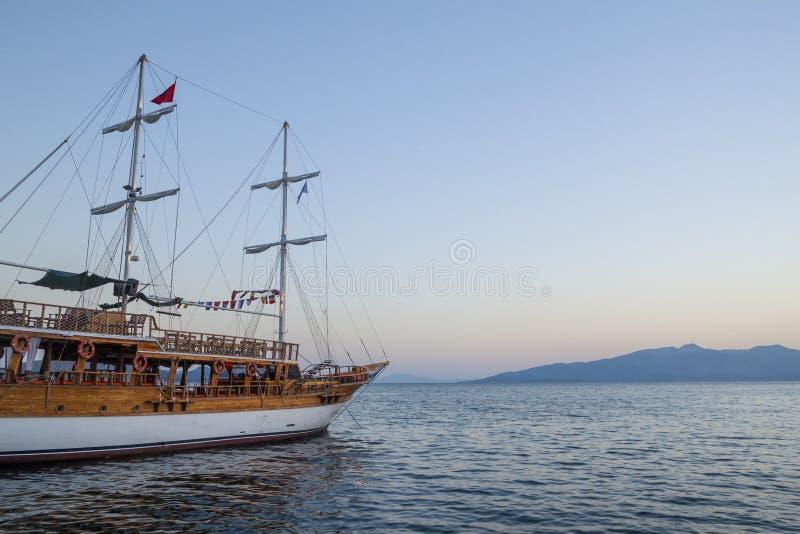 Vintage Mast Holzsegel-Schiff für Seereisen im Hafen von Saranda, Albanien bei Sonnenuntergang oder Sonnenaufgang Meereslandschaf lizenzfreie stockfotos