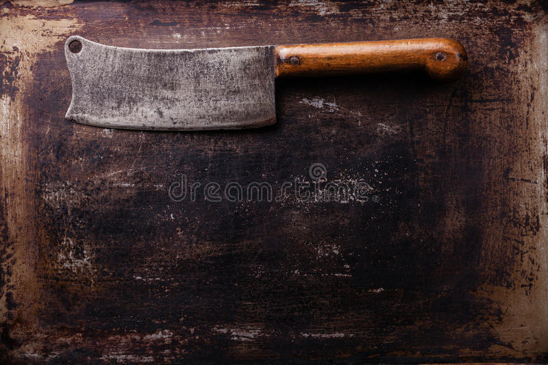 Vintage Meat cleaver on black background. Vintage Meat cleaver on old scratched black dark background texture stock photos