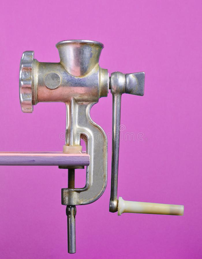 Vintage meat grinder on violet pastel background, creative and conceptual photo, minimalist trend. Vintage meat grinder on violet pastel background, creative royalty free stock photos